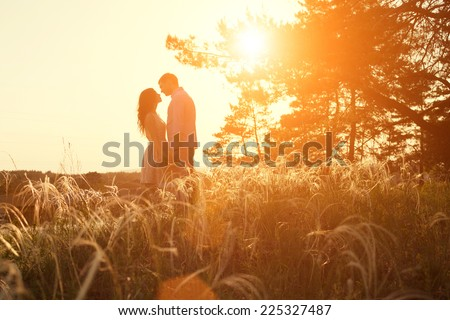 young couple kissing on the background of a sunset in the field - stock photo