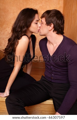 Young couple kissing on the stairs at home - stock photo