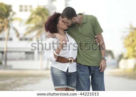 Young couple kissing outdoors - stock photo