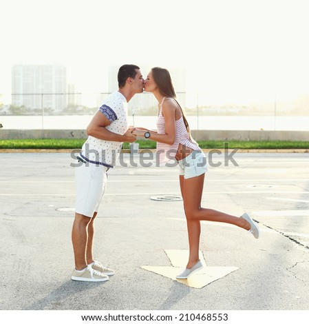 young couple kissing over sunset. - stock photo