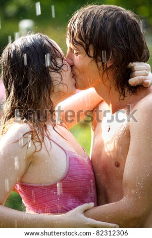 Young couple kissing under the rain - stock photo