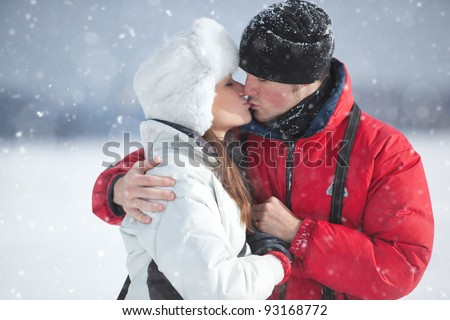 Young couple kissing winter outdoors portrait. - stock photo
