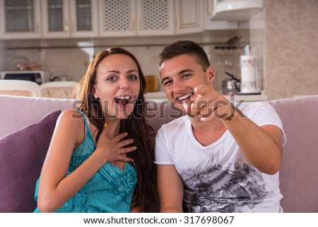 Young Couple Laughing and Pointing at Camera - Man and Woman Enjoying Television Program or Film Together While Sitting on Sofa at Home - stock photo