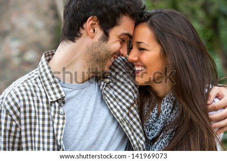 Young couple laughing with heads together outdoors. - stock photo