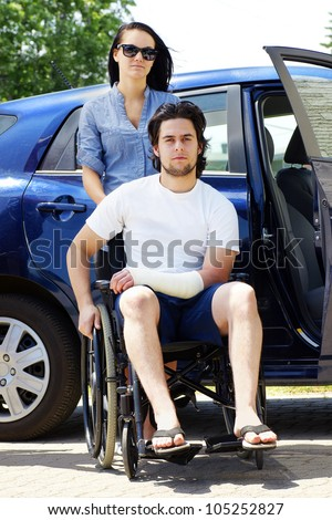 Young couple leaving or arriving to the hospital,young man in wheelchair with a cast on his hand. - stock photo