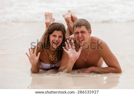 Young couple lie on the ocean beach. - stock photo