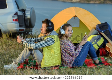 Young couple listening to an mp3 player in a tent - stock photo