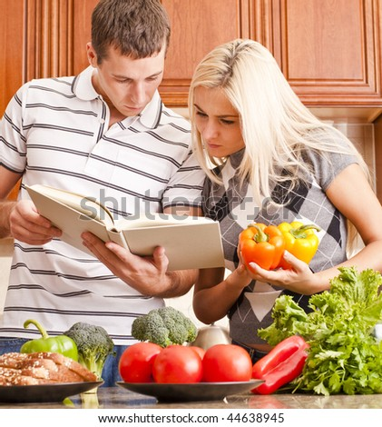 Young couple look at a recipe book in the kitchen. The counter is full of fresh vegetables. Square shot. - stock photo