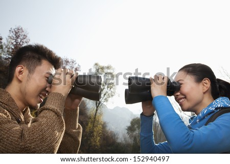 Young couple looking at each other through binoculars - stock photo