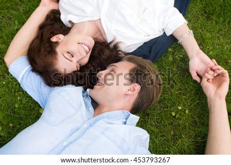 Young couple looking at each other while lying down on the grass - stock photo