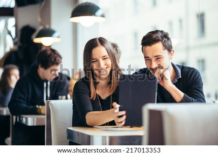 Young couple looking at photos on tablet computer laughing in cafe - stock photo