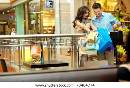 Young couple looking at their shopping bags - stock photo