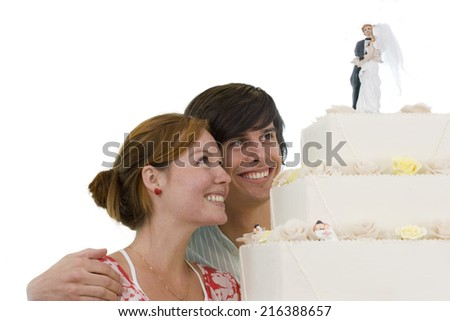Young couple looking at wedding cake, smiling, cut out - stock photo