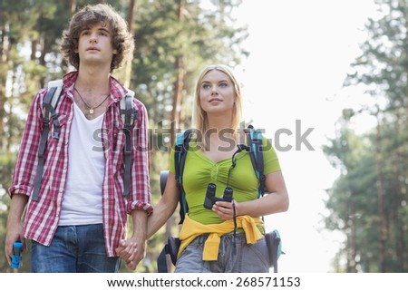 Young couple looking away while hiking in forest - stock photo