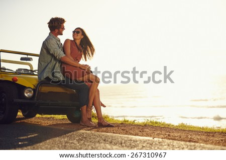 Young couple looking into each other's eyes. Romantic young couple sitting on hood of their car enjoying the moment, outdoors with copy space. Young couple in love on a road trip. - stock photo