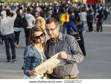 Young couple looking on a map in a crowded city street in Paris, France. - stock photo