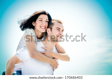 Young couple looking to bright future - happy woman embracing her love around neck - stock photo