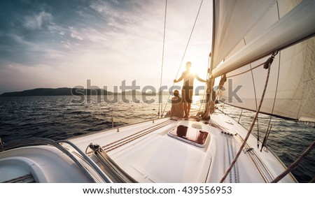 Young couple looking to the sunset on the yacht in Andaman sea - stock photo