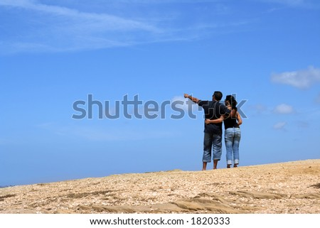 Young couple looking up together with sky background. - stock photo