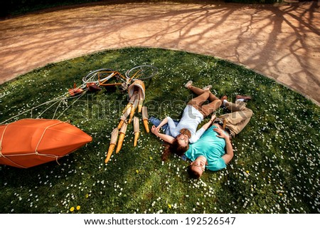 Young couple lying and dreaming on the grass in the park with bicycle with red dirigible and basket with baguettes, top view, general plan - stock photo