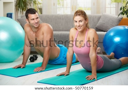Young couple lying on  fitness mattress and streching abdominal. - stock photo