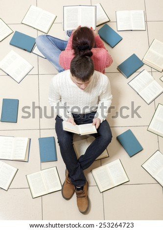 Young couple lying on floor with books and reading, top view. Blurred text is unreadable - stock photo