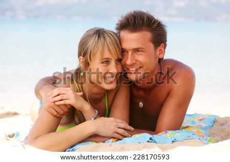 Young couple lying on the beach - stock photo
