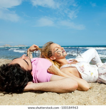 Young couple lying together on a sand by sea and looking to a sky - stock photo