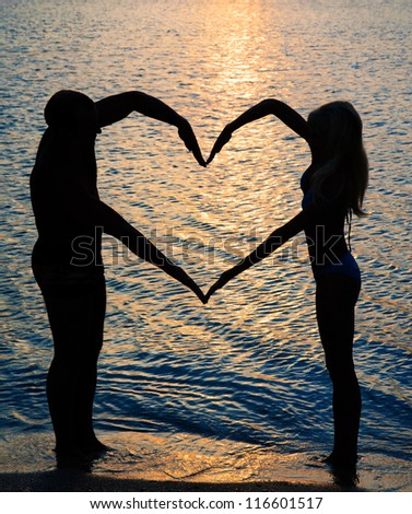 young couple making heart shape with arms on beach against golden sunset - stock photo