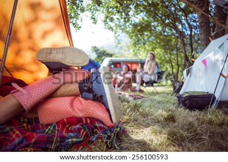 Young couple making out in tent at a music festival - stock photo