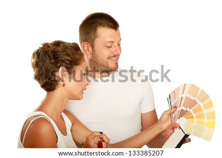 Young couple making repairs in the paint, isolated on white background - stock photo
