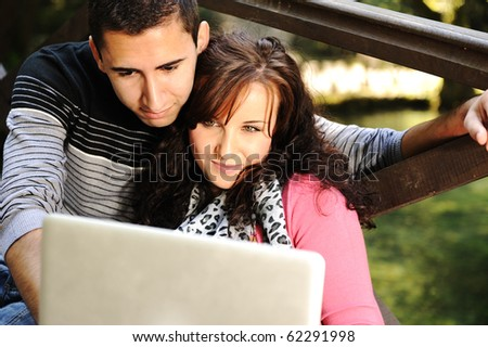 Young couple, male and female sitting in park and studying and workin together with notebook (laptop) - stock photo