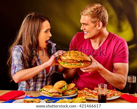 Young couple male and woman eating hamburgers . Fastfood concept.  Very big fast food hamburgers. - stock photo
