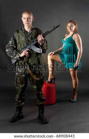 Young couple, male model dressed in military and female model dressed in civilian, pose in studio - stock photo