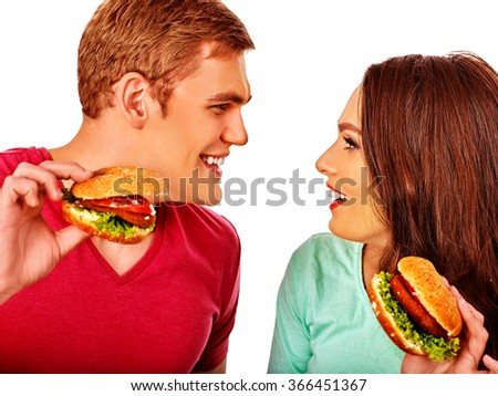 Young couple man and woman flirting and eating hamburgers  . Fastfood concept.  Isolated. - stock photo