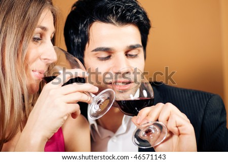 Young couple - man and woman - in a restaurant drinking glasses of red wine; focus on the face of woman - stock photo