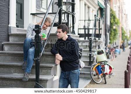 young couple, man and woman in Amsterdam, Netherlands, woman is sitting on stairs with smart phone, man in talking with her - stock photo