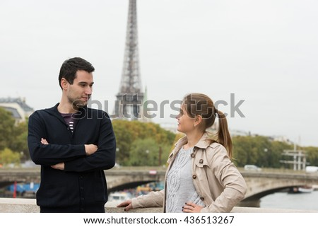 young couple man and woman standing on the bridge on river Seine, Paris, France, in front of Eiffel Tower, having conversation - stock photo
