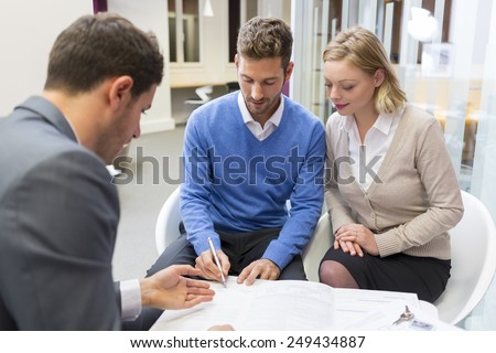 Young couple meeting real-estate agent for house investment. Signing a contract - stock photo