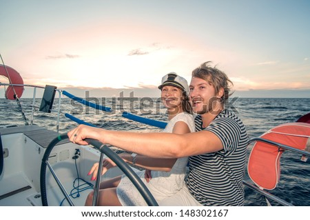 Young couple navigating on a yacht - stock photo