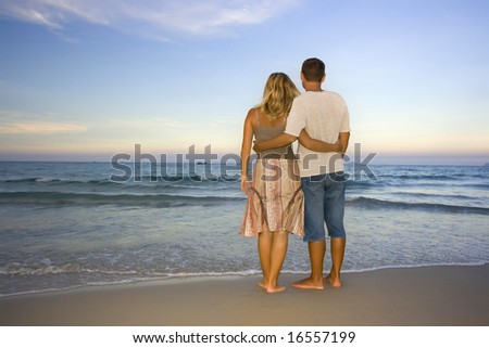 Young couple near the ocean on sunset time - stock photo