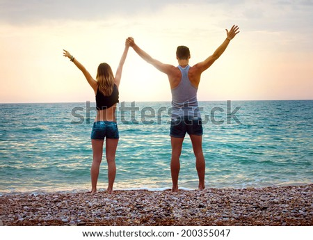 Young couple near the sea at sunset with arms raised - stock photo