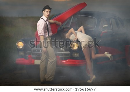 Young couple  next retro car  in smoke - stock photo