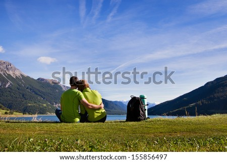 young couple of backpackers near the lake in mountains - stock photo