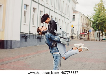 young couple of hipsters in a leather jacket jeans t-shirt, posing on the street, romantic kiss at sunset, a tender embrace, wedding, girlfriend and boyfriend, lovers outdoor portrait,together forever - stock photo