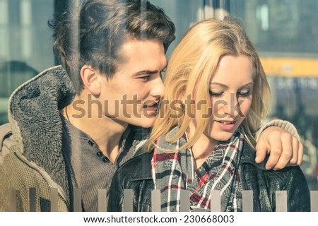 Young couple of lovers behind glass reflections - Handsome man whispering magic words in the ear of his beautiful girlfriend - Beginning of a love story on a warm vintage filtered look - stock photo