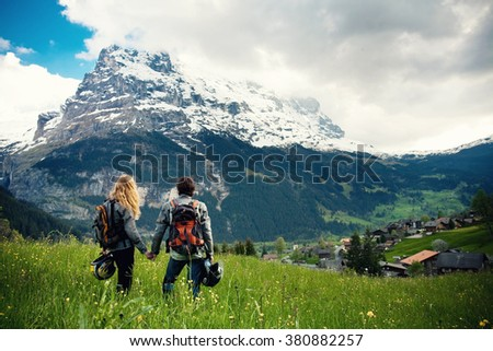 Young couple of motorcycle travelers enjoying a valley view in the summer mountains of Switzerland, Grindelwald. Moto tourism and moto travellers lifestyle while traveling Europe - stock photo