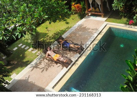 young couple of people relax on villa by swimming pool - stock photo