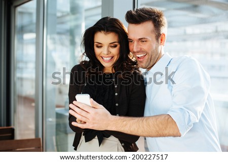 Young couple of professionals browsing massages on the phone - stock photo