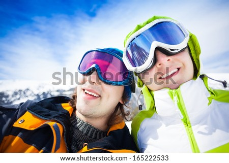 Young couple of snowboarders with mountains on background - stock photo
